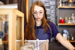 Nettes Mädchen barista, welches die Rechnung im Kaffeehaus auf der Tablette zählt stockfoto