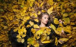 Nettes Mädchen bedeckt mit herbstlichen Blättern Junge Frau, die aus den Grund umfasst durch Herbstlaub im Park niederlegt Schöne Stockfotografie