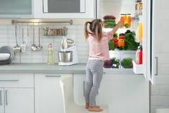 Nettes Mädchen, das Apfel aus Kühlschrank heraus nimmt stockfotografie