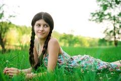 Nettes Mädchen, das auf dem Gras aufwirft Stockfotografie