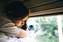 Nettes Mädchen, das auf dem obersten Regal im Zug liegt und heraus das Fenster schaut stockfoto