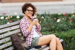 Nettes Mädchen, das auf der Bank sitzt Stockbild