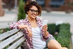Nettes Mädchen, das auf der Bank sitzt Lizenzfreies Stockbild