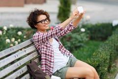 Nettes Mädchen, das auf der Bank sitzt Lizenzfreie Stockbilder