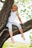 Nettes Mädchen, das auf einem Baum im Sommer sitzt Lizenzfreie Stockfotografie