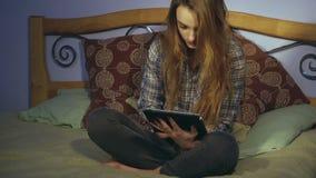 Nettes Mädchen, das auf einem Bett sitzt und eine digitale Tablette untersucht stock video footage