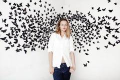 Nettes Mädchen, das auf einem fantastischen Hintergrund mit vielen Schmetterlingen steht Lizenzfreie Stockbilder
