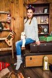 Nettes Mädchen, das auf einem Koffer gegen den Hintergrund des Chri sitzt Stockfoto