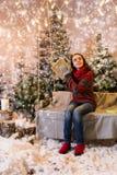 Nettes Mädchen, das auf einem Schwingen mit einer Decke unter der Taschenlampe sitzt Lizenzfreie Stockfotografie