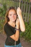 Nettes Mädchen, das auf einem Seilschwingen in der Landschaft schwingt Stockfoto