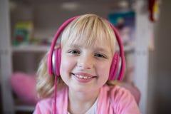 Nettes Mädchen, das auf rosa Kopfhörer hört stockfotografie