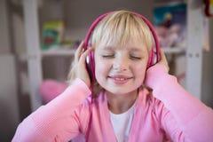 Nettes Mädchen, das auf rosa Kopfhörer hört stockfotos