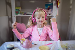 Nettes Mädchen, das auf rosa Kopfhörer hört lizenzfreie stockbilder