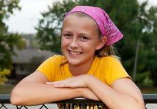 Nettes Mädchen, das auf Zaun-Schiene sich lehnt lizenzfreies stockfoto