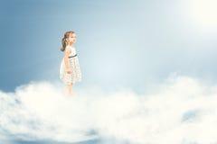 Nettes Mädchen, das barfuß auf Wolken steht Stockfoto