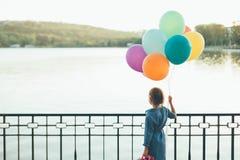 Nettes Mädchen, das bunte Ballone und kindischen Koffer L hält Stockfotografie