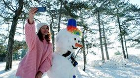 Nettes Mädchen, das in der Hand Foto mit einem Schneemann, Winter selfie, Handy einer jungen Frau herein macht Spaß selfie Foto m stock footage