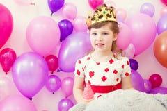 Nettes Mädchen, das in der Krone auf Ballonhintergrund aufwirft Stockfotos