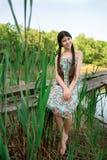 Nettes Mädchen, das in der Waldfront den See sitzt Lizenzfreie Stockfotografie