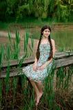 Nettes Mädchen, das in der Waldfront den See sitzt Lizenzfreie Stockfotos