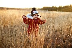 Nettes Mädchen, das durch ein Feld am Sonnenuntergang läuft Lizenzfreies Stockbild