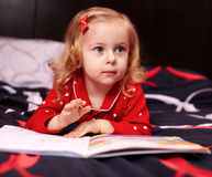 Nettes Mädchen, das ein Buch auf dem Bett liest Lizenzfreies Stockbild