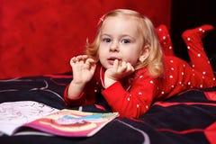 Nettes Mädchen, das ein Buch auf dem Bett liest Lizenzfreie Stockfotos