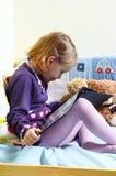 Nettes Mädchen, das ein Buch auf ihrem Bett mit Spielwaren um sie liest Lizenzfreie Stockfotos