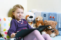 Nettes Mädchen, das ein Buch auf ihrem Bett mit Spielwaren um sie liest Stockfotografie