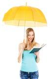 Nettes Mädchen, das ein Buch unter Regenschirm liest stockbilder
