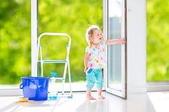 Nettes Mädchen, das ein Fenster wäscht Stockfoto