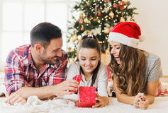 Nettes Mädchen, das ein Geschenk auf einem Weihnachtsmorgen mit ihrer Familie öffnet Stockfotografie