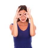 Nettes Mädchen, das ein lustiges Gesicht mit Gläsern gestikuliert Lizenzfreie Stockbilder