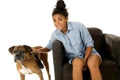 Nettes Mädchen, das in einem Stuhl mit ihrem Hund einen Boxer nahe bei ihr sitzt lizenzfreies stockfoto