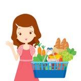 Nettes Mädchen, das Einkaufskörbe voll vom Essen hält Lizenzfreie Stockbilder