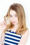Nettes Mädchen, das Haar auf dem Finger beflügelt Stockfotos