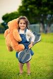 Nettes Mädchen, das im Grasholding-Teddybären steht lizenzfreies stockfoto