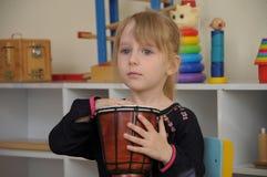 Nettes Mädchen, das im Kindergarten trommelt lizenzfreies stockbild