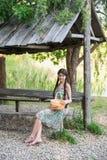 Nettes Mädchen, das im Wald mit Korb sitzt Stockfoto