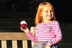 Nettes Mädchen, das kleinen Kuchen isst stockbilder