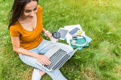 Nettes Mädchen, das Laptop bei der Entspannung auf Gras verwendet Lizenzfreies Stockbild