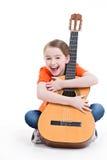 Nettes Mädchen, das mit Akustikgitarre sitzt. Lizenzfreie Stockfotografie