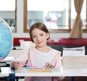 Nettes Mädchen, das mit Büchern und Kugel am Schreibtisch lächelt Stockbild