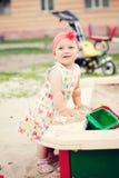 Nettes Mädchen, das mit dem Sand spielt Stockbild