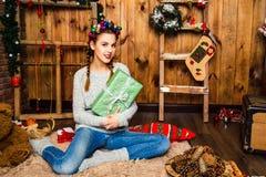 Nettes Mädchen, das mit einem Geschenk auf einem Hintergrund des Weihnachtsdekors sitzt Stockfotografie