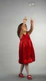 Nettes Mädchen, das mit Seifenluftblasen spielt Stockfoto