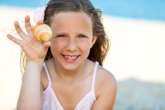 Nettes Mädchen, das Muschel auf Strand zeigt. Lizenzfreies Stockfoto
