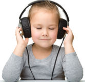 Nettes Mädchen, das Musik unter Verwendung der Kopfhörer genießt Lizenzfreie Stockfotos