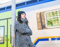 Nettes Mädchen, das nahe bei einem Zug wartet Stockfotos