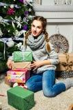 Nettes Mädchen, das nahe dem Weihnachtsbaum in einem Reinraum sitzt Neues Y Lizenzfreies Stockfoto